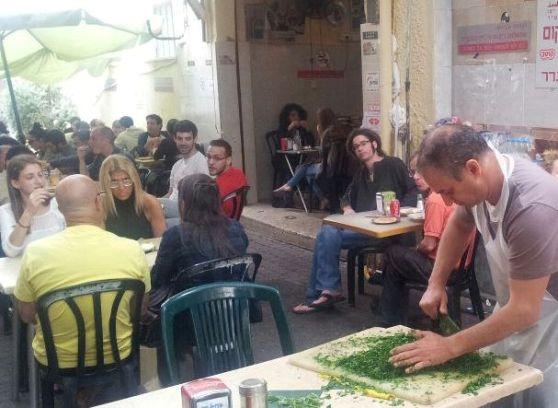 chopping fresh parsley at Shlomo and Doron Hummus in Tel Aviv