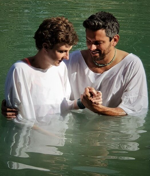 Tourists undergo a baptism in the Jordan River on a private tour with Levi of Go-TelAviv tours