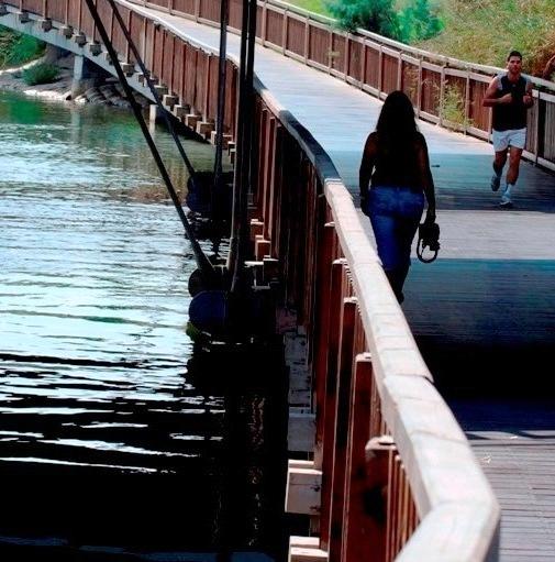 Jogging and walking along a bridge in Tel Aviv's beautiful Yarkon Park